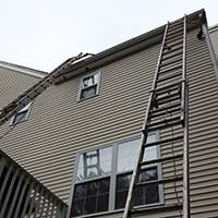 extension ladders with stand - offs placed on tall house